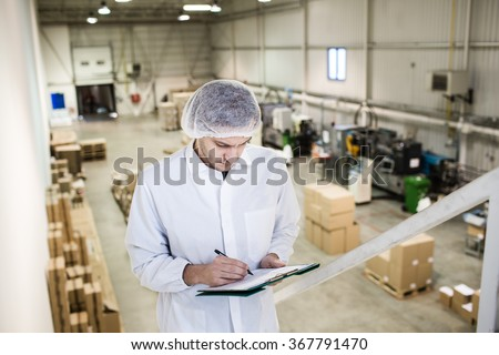 Worker In warehouse for food packaging. Manager writing on clipboard in automated production line at modern factory. View from above. Color toned image.