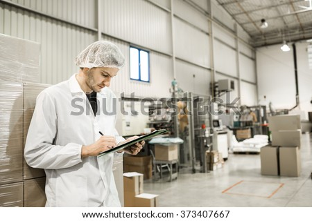 Worker In warehouse for food packaging. Manager writing on clipboard in automated production line at modern factory. Color toned image.