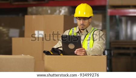 Worker in warehouse using digital tablet