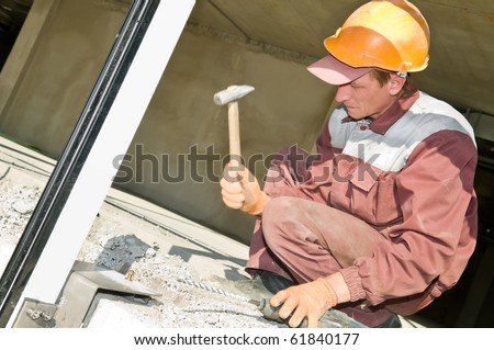 worker in work uniform hammering a screw in concrete