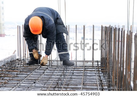 worker in workwear making reinforcement metal framework for concrete pouring