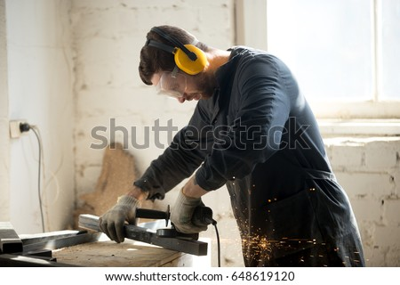 Worker in workwear, protective glasses, hearing protection headphones, gloves using dangerous electric power tools in loft workshop. Safety at workers workplace, personal protective equipment concept
