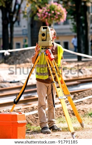 Worker inspecting site  with his tripod and industrial device