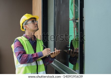 Worker, inspector, engineer is checking building structure around window with checklist in hand. Inspect and checking concept Photo stock ©