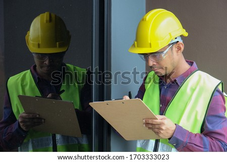 Worker, inspector, engineer or auditor is checking building structure around window with checklist clipboard in hand. Inspection, quality checking and audit concept Foto d'archivio ©