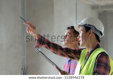 Worker, Inspector is checking with checklist and pointing new building with customer or client. Inspection and engineering concept