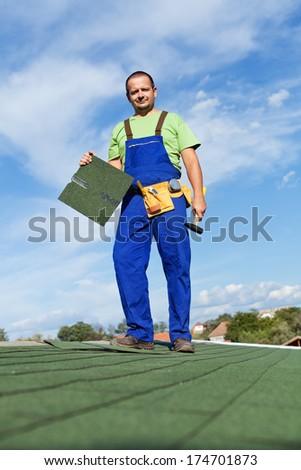 Worker installing bitumen roof shingles - standing on top of building