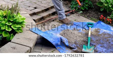 Worker installing pipe under lock stone walk for residential sprinkler system. Garden dirt on blue tarp with shovel   Сток-фото ©