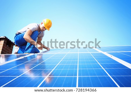 Worker installing solar panels outdoors
