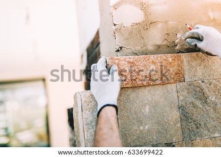 worker installing stone tiles in construction site. masonry details on exterior wall with trowel putty knife #633699422