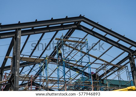 Shutterstock Worker installing structure of roof steel for new house