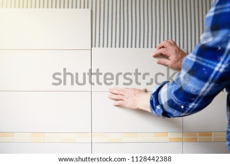 Worker installing tiles on wall #1128442388
