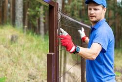 worker installing welded metal mesh fence
