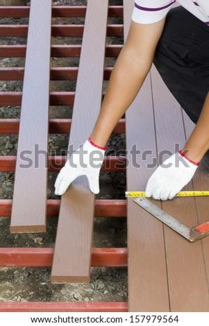 Worker installing  wood floor for patio