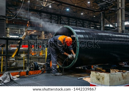Worker installs clamping ring on coated pipe