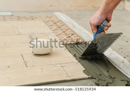 Worker installs  tiles on the floor. He put glue using comb trowel.