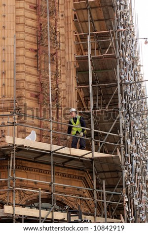 Worker is assembling a scaffolding on a department store in central London