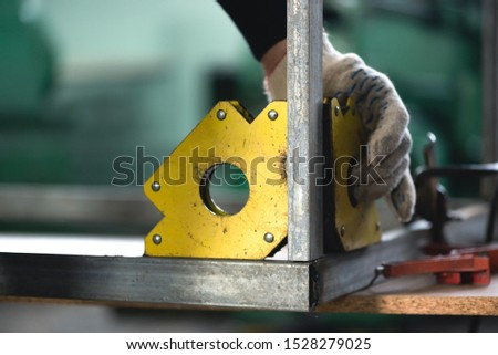 Worker is fixing a metal frame by magnetic square.