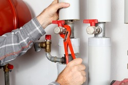 worker is fixing a valve in a heating room