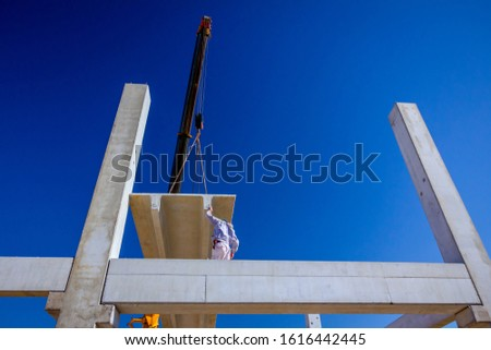 Worker is helping mobile crane to manage concrete joist for assembly huge construction.