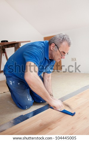 worker is laying laminate, man at work, lamiate lay