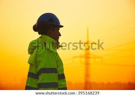 Worker is watching electricity pylons and substation at the sunset