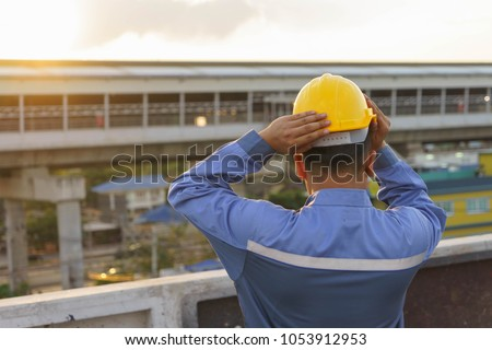 Worker is wearing his yellow helmet in the morning and ready to work. #1053912953