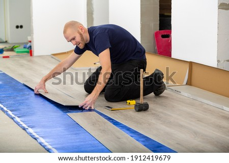 Worker joining click lock vinyl floor plank covering at home renovation. Man laying PVC-floor. Craftsman installing new laminated wooden floor on blue acoustic thermal flooring underlayment.