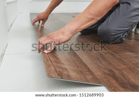 worker joining vinyl floor covering at home renovation Foto stock ©