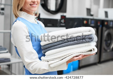 Worker Laundry girl holding fresh towels in her hands and smiles at the dry cleaners #424728877