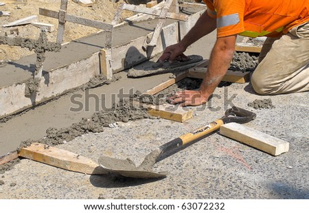 Worker laying concrete curb with spreader