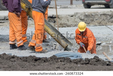 Worker leveling concrete poured from mixer on construction site