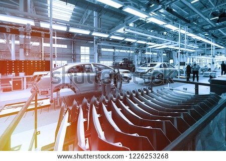 Worker looks into car body on production line. Factory for production of cars in blue. Modern automotive industry. Blue tone #1226253268