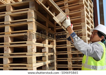worker man arranging  pallets in a warehouse