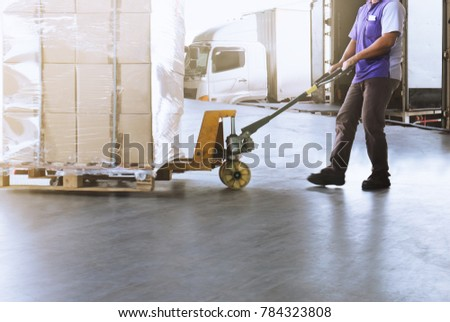 Worker man dragging hand pallet truck or manual forklift with the shipment pallet unloading into a truck.