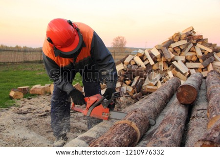 Worker man in an orange helmet sawing logs chainsaw in the village on the background of a pile of chopped wood in the autumn day on background of wood fence and green grass backyard #1210976332