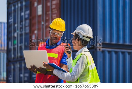 Worker man in hardhat and safety vest holding laptop and Female foreman talks on two-way radio control loading containers box from cargo ストックフォト ©