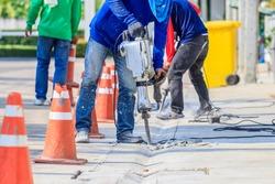 worker man mason drilling cement concrete floor with machine