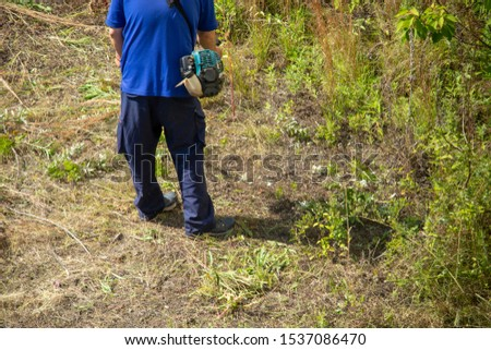 Worker man mowing grass with mower #1537086470