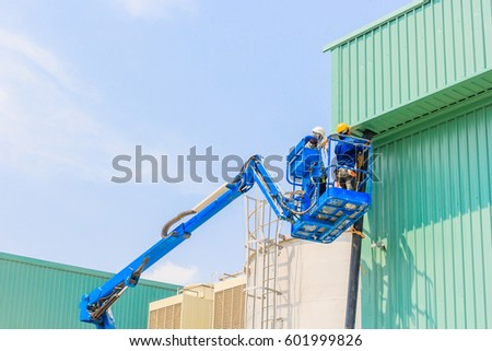 Worker man on a Scissor hydraulic Lift table Platform towards a factory roof at a construction site #601999826