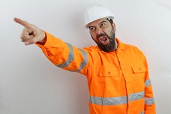 Worker man wearing hardhat and reflecting jacket showing and pointing with finger screaming and shouting anger rage.