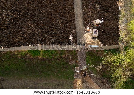 Worker manually makes a way to future parking lot. builder is busy with construction work. aerial view. manual labor concept