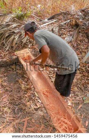 Worker manually processes the tree trunk and gouges with a simple trough tool. Heavy and demanding work with freshly cut trunks. Working place in nature. On the ground wooden chips and fallen leaves.