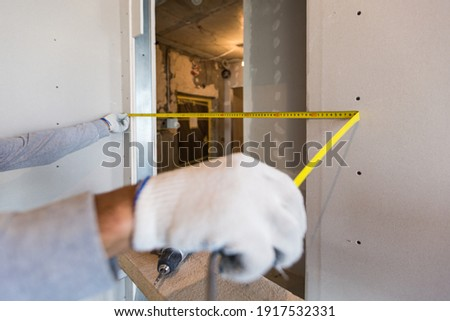 Worker measures distance in doorway after instaliing drywall in apartment that is under construction, remodeling, renovation, overhaul, extension, restoration and reconstruction . Concept of total Photo stock ©