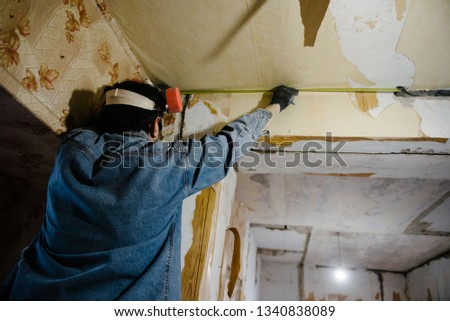 Worker measures distance using a tape measure