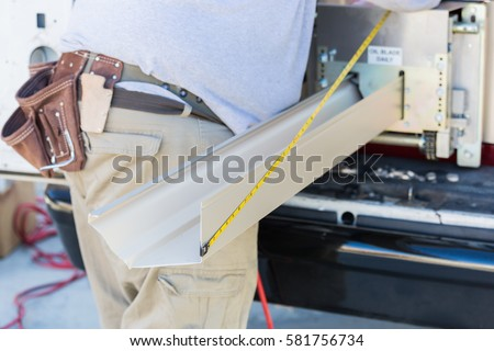 Worker Measuring An Aluminum Rain Gutter Feeding Through Seamless Shaping Machine.