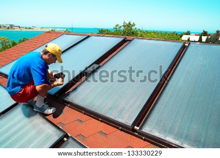 Worker mounting solar water heating panels on the roof