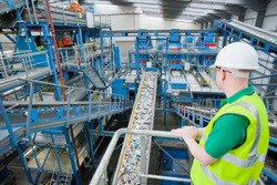 Worker observing plastic on conveyor belt in recycling plant