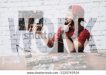 Worker of Computer Service Examines Motherboard. Man Makes Repair of Broken Computer Hardware. Concept of Professional Maintenance. Transparent Text. Young Pensive Man Makes Upgrade of Device. Stockfoto ©