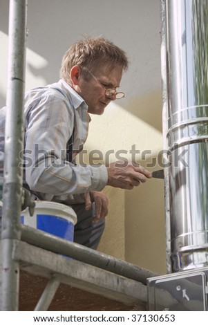worker on a scaffold fixing problems at house
